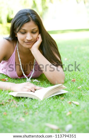 Portrait of an Indian girl reading a book while laying down on green grass in the park.