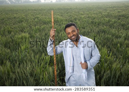 Portrait of an Indian man holding a stick - stock photo