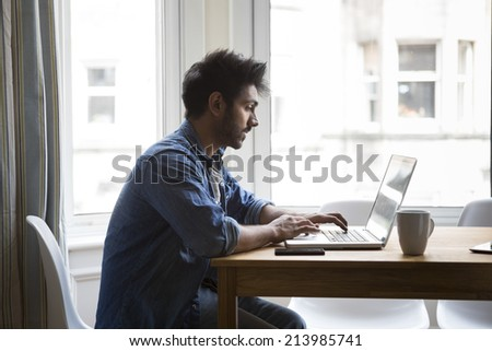 Portrait of an Indian man sitting at a table at home working on a laptop computer. Side View. - stock photo