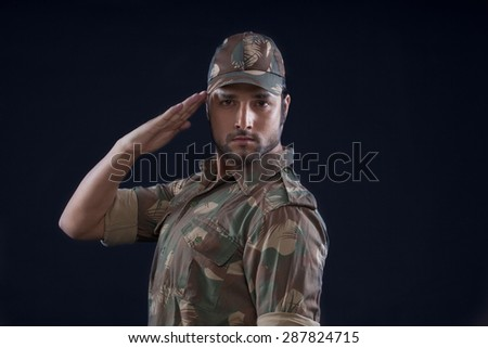Portrait of an Indian soldier saluting - stock photo