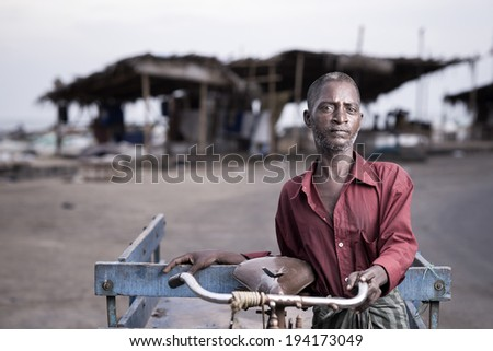 Portrait of an indian tricycle worker  - stock photo