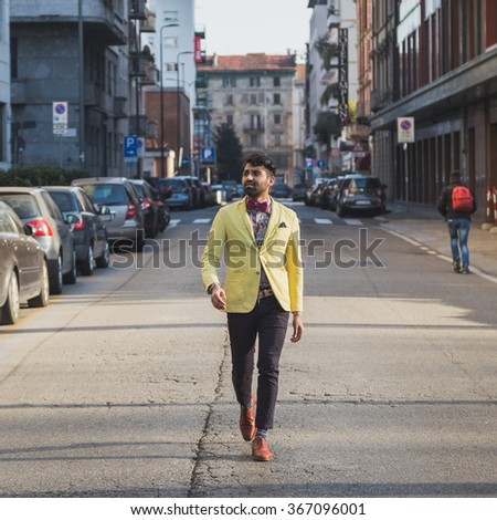 Portrait of an Indian young handsome man walking in an urban context