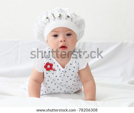 portrait of an infant baby girl wearing a hat - stock photo
