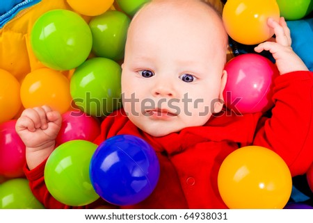 Portrait of an infant lying in basin with colorful balls - stock photo