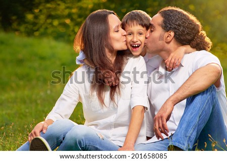 Portrait of an international family sitting together in the park - stock photo