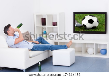 Portrait Of An Mature Man Watching Soccer Game On Television - stock photo