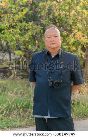 Portrait of an old asian man hanging camera on tree leaves background in garden.
