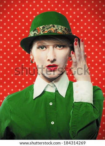 Portrait of an old-fashioned woman in a green hat, red polka dot background