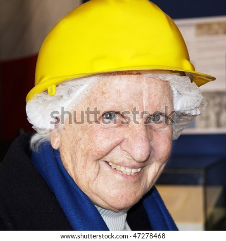 portrait of an old lady wearing a net and a hard construction hat just before taking a tour of war shelters for safety - stock photo