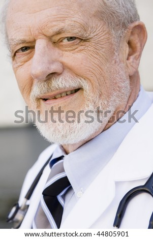 Portrait of an Old Male Doctor Smiling Directly To Camera - stock photo