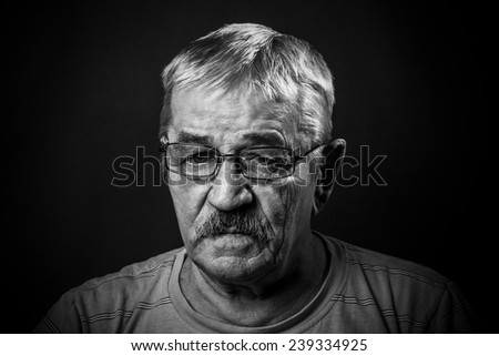 portrait of an old man in glasses - stock photo