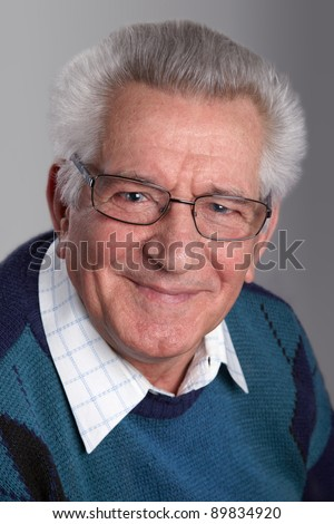 Portrait of an old man smiling, looking at camera, in studio. - stock photo