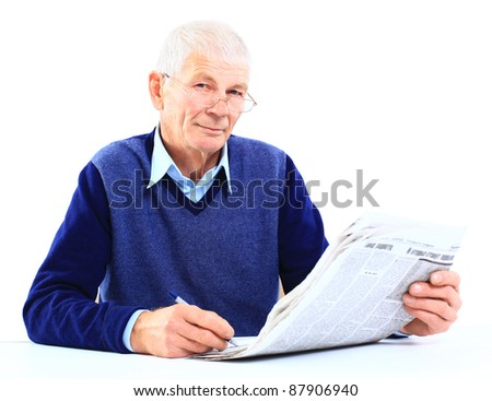 Portrait of an old man solving crosswords in the newspaper - stock photo