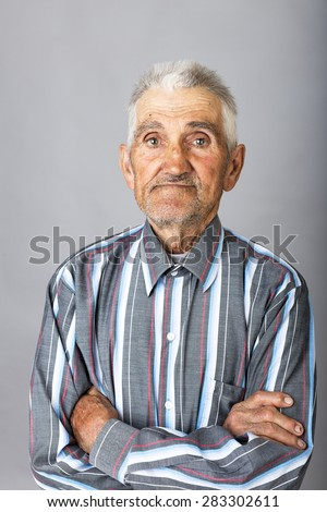 Portrait of an old man with arms folded over gray background - stock photo