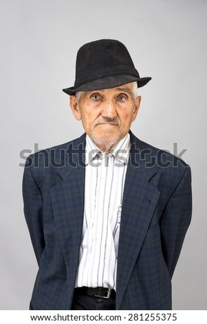 Portrait of an old man with hat over gray background