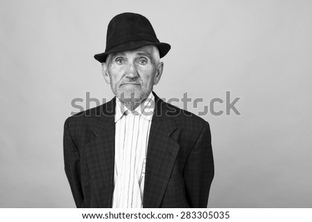 Portrait of an old man with hat over gray background - stock photo