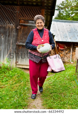 Portrait of an old rural lady holding a pumpkin - stock photo