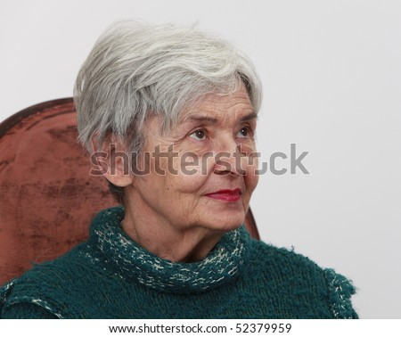 Portrait of an old woman against a gray background