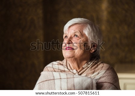 Portrait of an old woman are bundled up in blanket