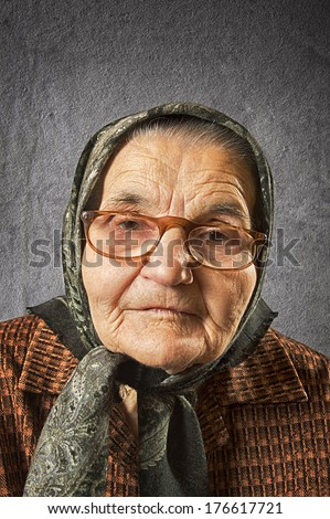 Portrait of an old woman on a vintage background, dreaming the past. Soft focus. - stock photo