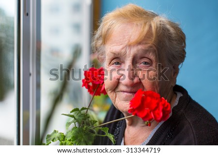 Portrait of an old woman on the balcony with red flowers. - stock photo