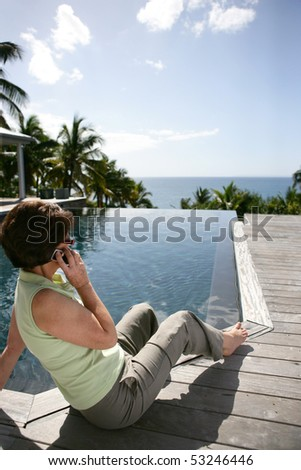 Portrait of an old woman phoning in front of a swimming pool