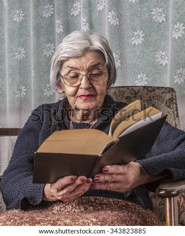 Portrait of an old woman reading a book. - stock photo