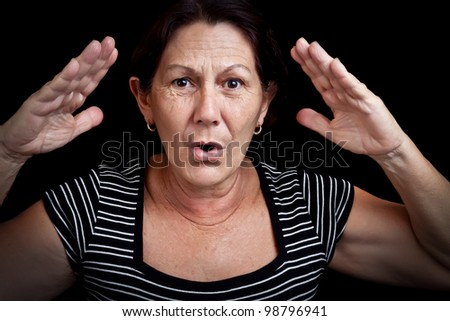 Portrait of an old woman screaming and gesturing with her hands isolated on a black background - stock photo