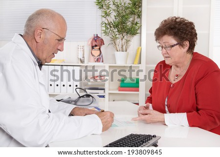 Portrait of an older doctor talking with his female patient. - stock photo