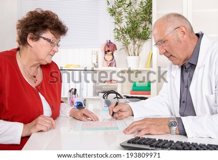 Portrait of an older doctor with experience smiling at desk. - stock photo