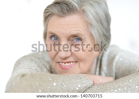 Portrait of an older woman in a gray sweater at home