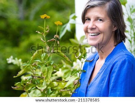 portrait of an older woman on her balcony and smiling - stock photo