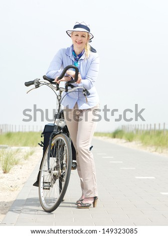 Portrait of an older woman relaxing with bike on countryside path - stock photo