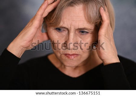 portrait of an older woman with a headache on a gray background