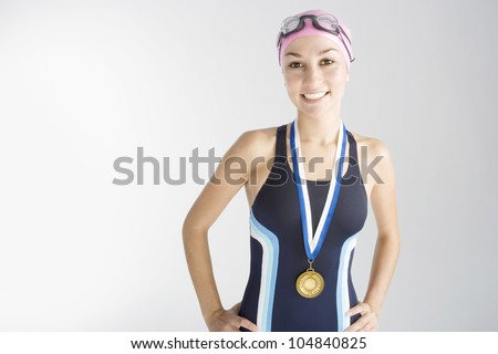 Portrait of an olympic swimmer wearing a gold medal and smiling at the camera. - stock photo