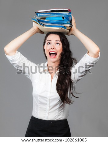 Portrait of an over worked business woman with a big pile of folders on her head - stock photo