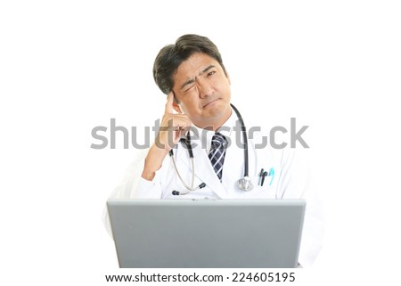 Portrait of an overworked and tired Asian doctor - stock photo