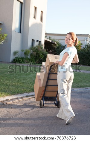 Portrait of an pretty woman with stack of box moving to a new house - stock photo