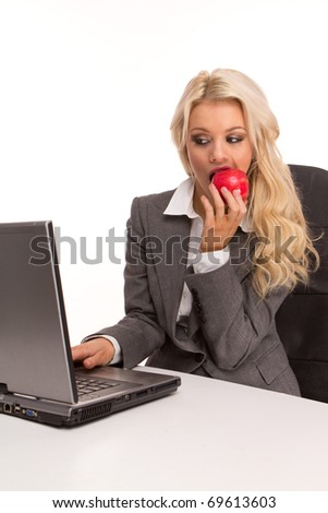 Portrait of an sexy business woman sitting by a desk and laptop eating red apple for a breakfast