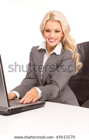 Portrait of an sexy business woman sitting by a desk and laptop. studio shoot - stock photo