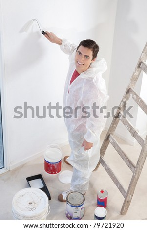 Portrait of an smiling workman painting the wall with a roller - stock photo