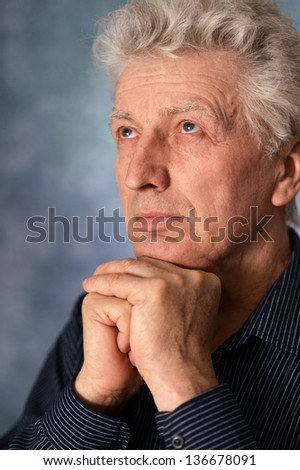 portrait of an thinking older man over gray background