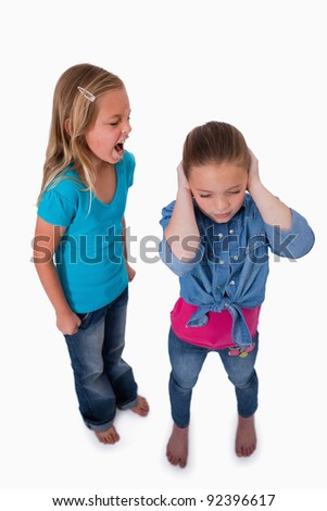 Portrait of an unhappy girl screaming at her friend against a white background - stock photo
