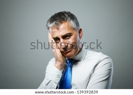 Portrait of an unhappy middle-aged businessman - stock photo