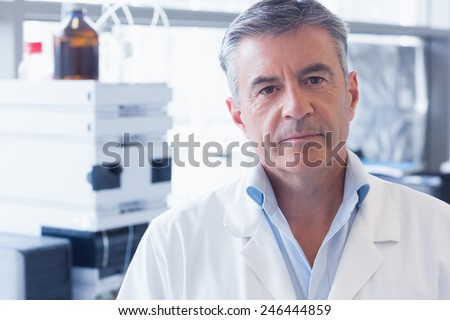 Portrait of an unsmiling scientist wearing lab coat in laboratory - stock photo
