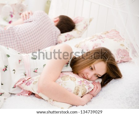 Portrait of an upset young woman lying separately from husband on the bed - stock photo