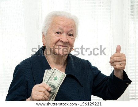 Portrait of an  woman holding money in hand and showing yes sign on white background - stock photo
