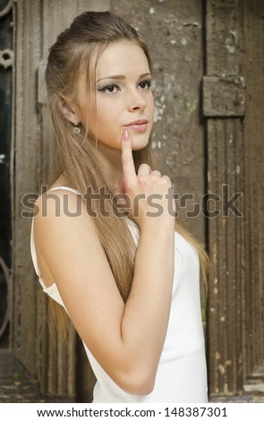 Portrait of an young, beautiful and attractive girl on old wood door background - stock photo