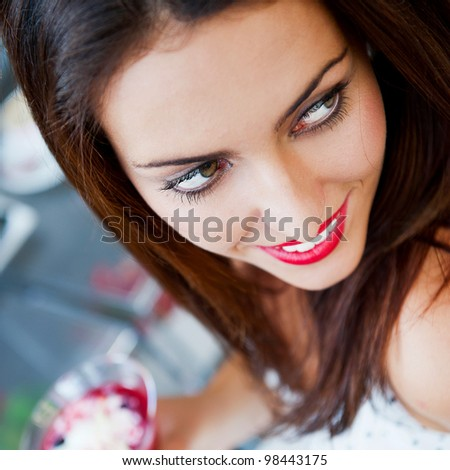 Portrait of an young beautiful woman eating an ice cream in cafe and looking at camera. Beautiful lovely eyes - stock photo
