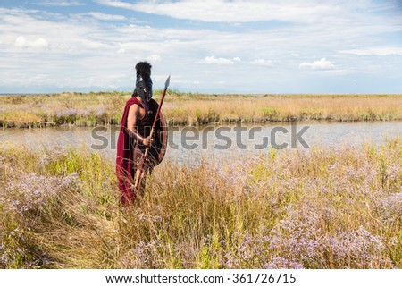 Portrait of ancient warrior in armor with spear, shield and Helmet. Spartan Soldier. Landscape background - stock photo